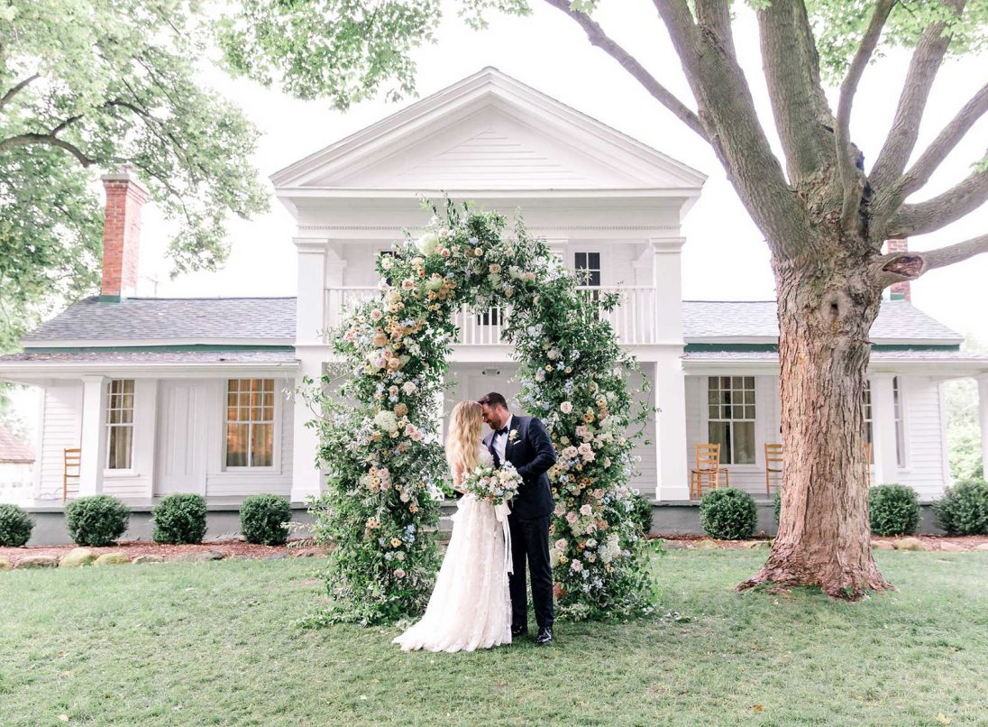 Bride and groom kissing at the wedding ceremony in front of the Zingerman's farmhouse