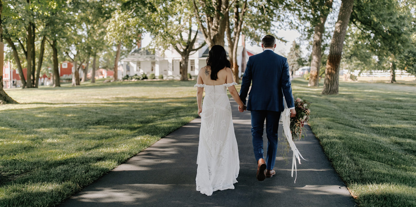 Bride and groom walking along Zingerman's Cornman Farms pathway