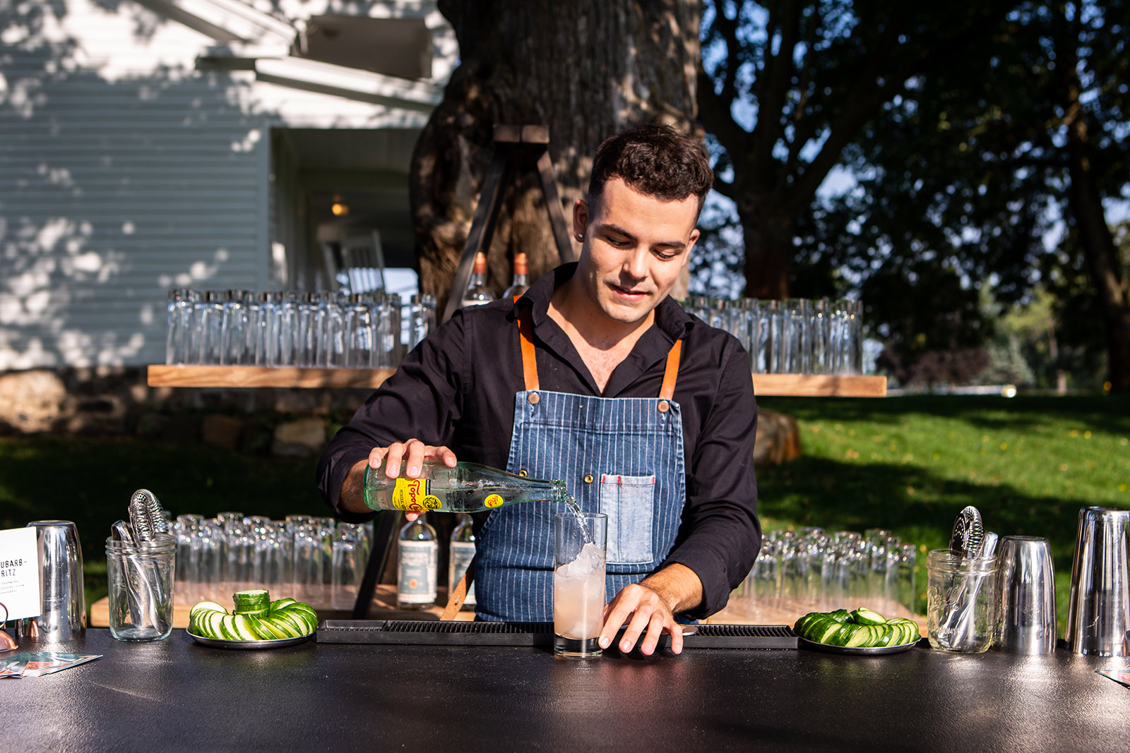 bartender making a drink at a bar outside