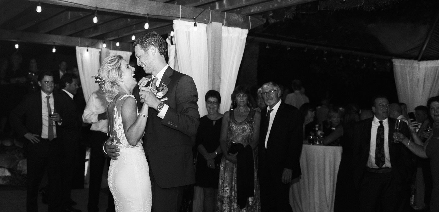 just married couple dancing together and laughing, guests looking at them