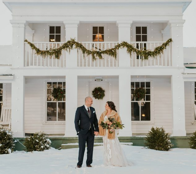 Bride and groom in front of the Zingerman's farmhouse for their winter wedding