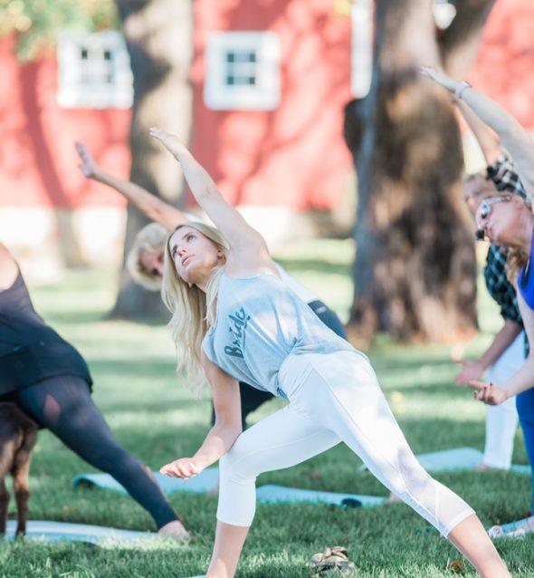 Group of women do yoga outdoors