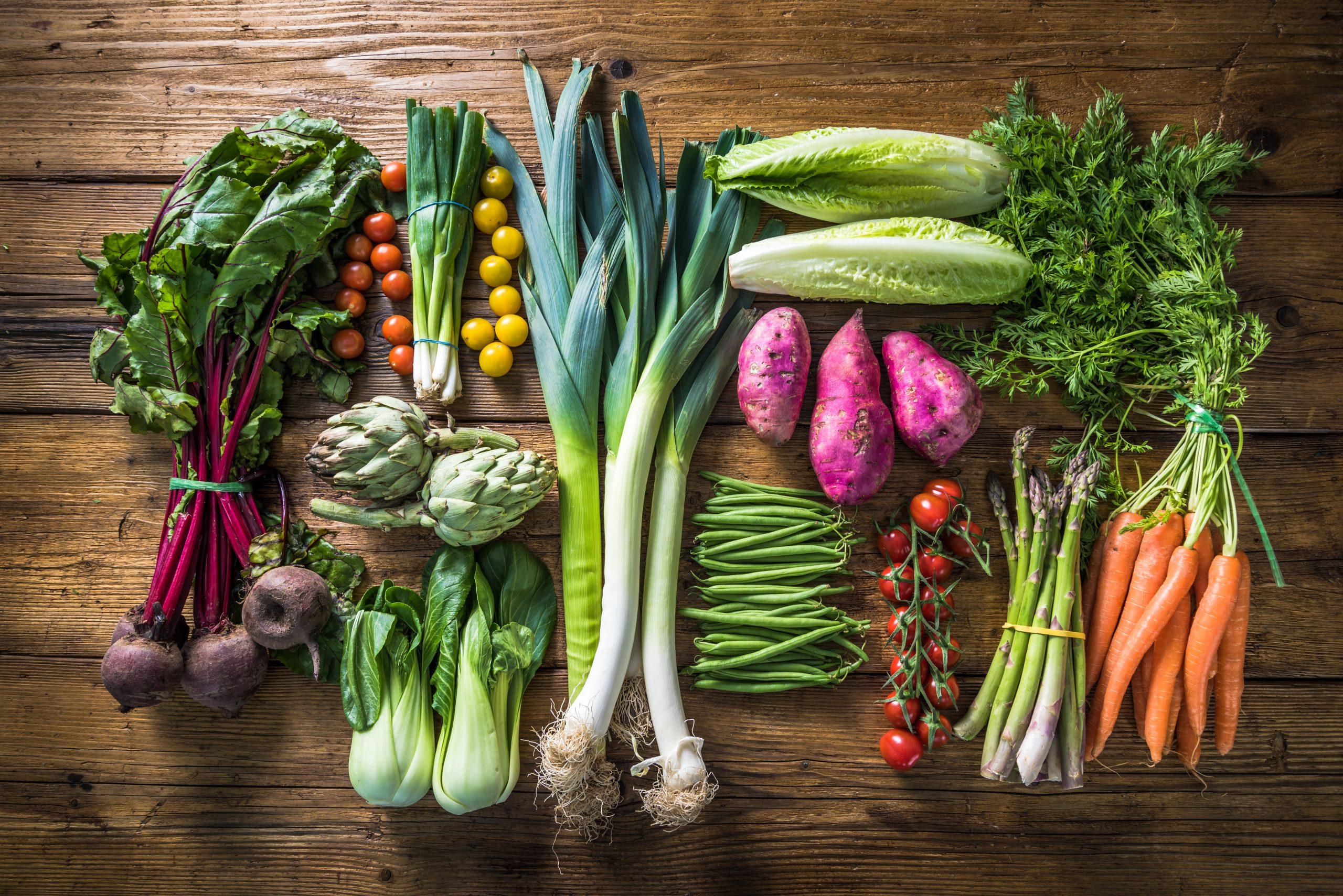 Exposition of fresh organic vegetables on wooden table. Beet, green onion, tomato, artichoke, bok choy, leek, lettuce salad, purple potato, green beans, asparagus, carrot and coriander.