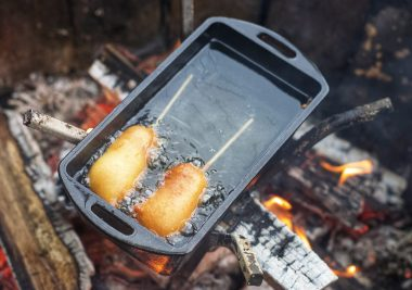 Corn dogs in pan over fire