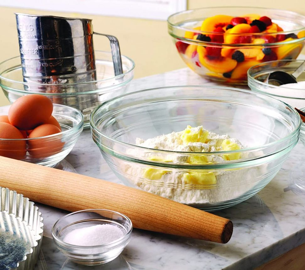 Images of eggs, peaches, butter and flower in glass mixing bowls on a table