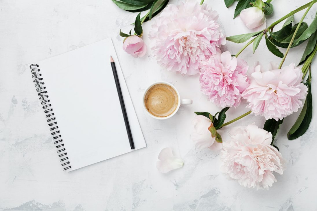 Wedding planning notebook with a cup of coffee and flowers