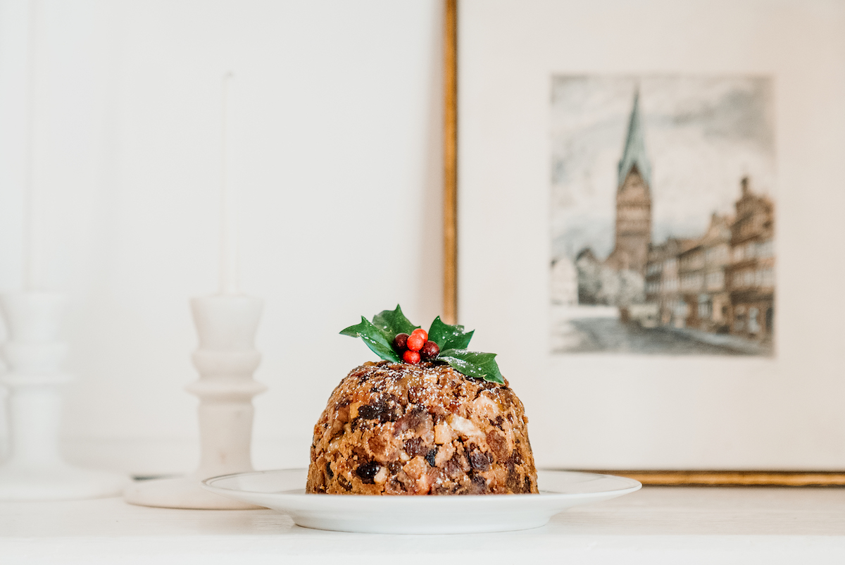 Christmas pudding on a plate with a sprig of holly.